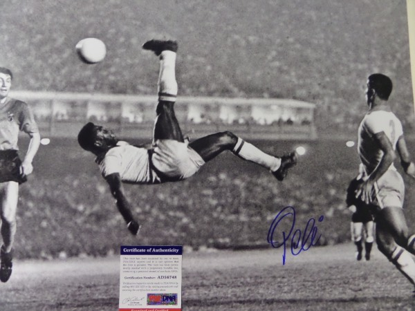 This large black and white 16x20 photo shows soccer legend Pele in a mid air bicycle kick.  It is hand-signed boldly in blue sharpie by the all time great himself, grading a strong 9 overall, and comes certified by PSA/DNA (AD 56748) for authenticity purposes.  A MUST for any soccer collection, and valued well into the hundreds!