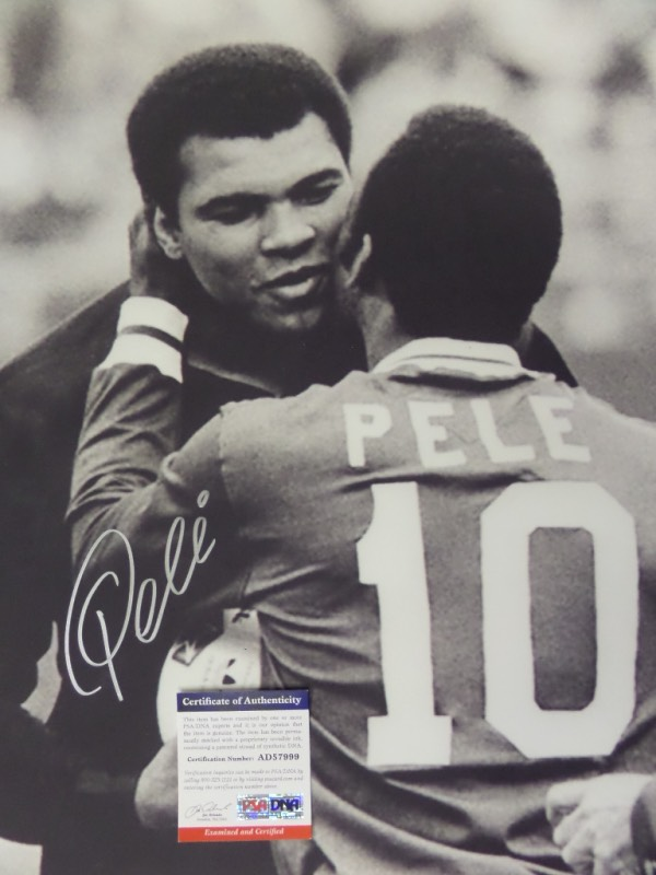 This HUGE black and white 16x20 photo shows soccer legend, Pele, embracing three time Heavyweight Champion, Muhammad Ali.  It is beautifully-penned in silver by the all time pitch great himself, and comes fully PSA/DNA certified (AD57999) for authenticity purposes.  A gorgeous display photo, ideal size for framing, and retail is well into the hundreds!