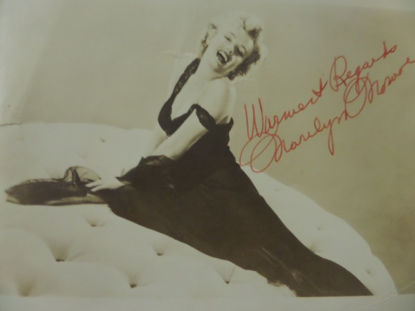 "This amazing, saved, vintage image is from when she just sarted in Hollywood and shows the late star posing and laughing on this sepia toned 6x8 beauty. It is in fine ciondition, exhibits some creasing and a repaired tear, and comes red ink signed with ""Warmest Regards"" written in her hand. It comes in the original 20th Century Fox mailer, and was signed a few years before she was known to the world."
