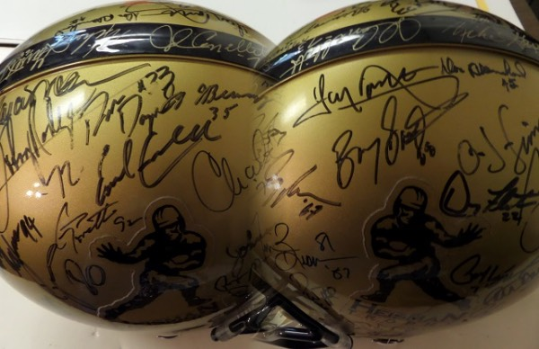 This authentic game style golf and black Heisman logo Riddell football helmet is hand-signed all over in black sharpie and gold paint pen by no less than 56 winners of the coveted college football award!  This might be the most complete in existence, featuring names like Berwanger, Blanchard, Davis, Jujack, Hart, Kazmaier, Lattner, Cassady, Hornung, Crow, Dawkins, Cannon, Bellino, Baker, Staubach, Huarte, Garrett, Spurrier, Beban, Simpson, Owens, Plunkett, Sullivan, Rodgers, Cappelletti, Griffin, Dorsett, Campbell, Sims, White, Rogers, Allen, Walker, Rozier, Flutie, Jackson, Testeverde, Brown, Sanders, Ware, Detmer, Howard, Torretta, Ward, Salaam, George, Wuerffel, Woodson, Williams, Dayne, Weinke, Crouch, White, Leinart, Bush and Smith.  Comes with a folder chock full of info and documentation, and includes holograms from both Tristar and Triumph.  This baby is the real deal, and is truly PRICELESS!