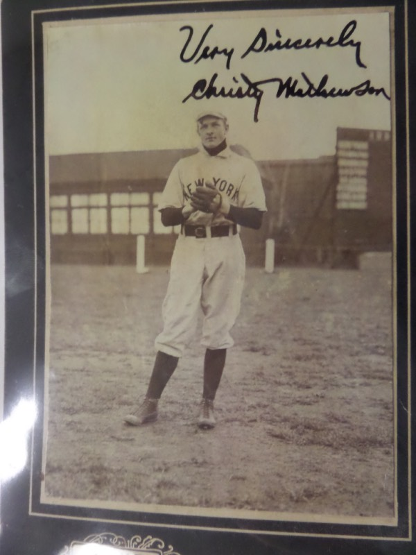 "This important signed photo shows the long gone ""Matty"" from his playing days, in a pitching pose, and in his old time NY Giants uniform. It is matted on a Henkel mat, measures near 5x7 in size, and has a hint of sepie tone to it. It is in VERY nice condition, comes black ink signed across the top, and that hi-value HOF signature grades about a 49 on a 1-10 scale!!! It can literally be seen from 50 feet away, and value is thousands..."