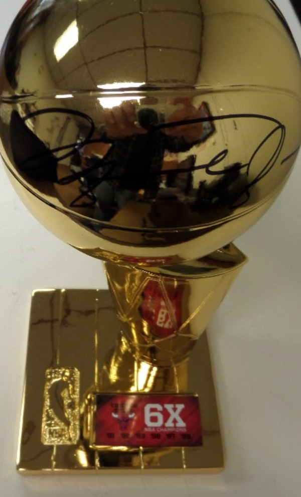 This stunning sports display piece is a super nice, VERY well made gold trophy, and free stands about a foot tall. It honors Mike, the Bulls and their 6 world championships, comes hand signed by the greatest baller ever in bold black sharpie, and grade is a 15 on a 1-10 scale. It comes int he Fanatics original box, and value is $1500.00 for sure.