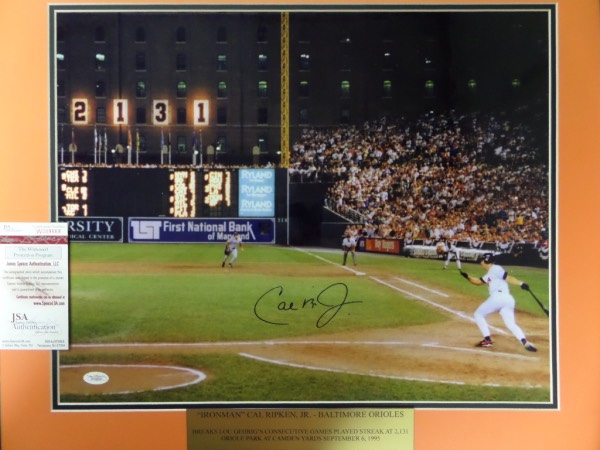 "This super nice, lifetime approved display is a HUGE 16x20 glossy Kodak photo, and from Cal's historic ""2131"" game in Baltimore. It was the 1995 moment where he broke Lou Gehrigs lifetime games streak and shows him at bat, and in mid-swing. It comes hand signed in perfect, large, bold blue sharpie, grade all over is a 15, and a custom engraved gold placard accompanies. It has a Jimmy Spence JSA LOA and lifetime hologram, and value in the super-size is $400.00."