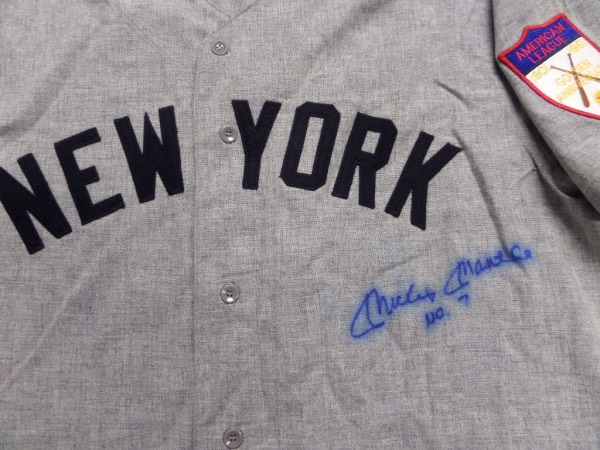 This road gray size XL 1951 New York Yankees throwback from Mitchell & Ness is in NM condition, and comes with everything sewn, including The Mick's 7 on the back, and an American League Golden Anniversary patch on the left shoulder.  It is front-signed in blue sharpie by the all time great himself, grading a slightly bled 6.5, with No. 7 added in his hand, and this baby will frame and show off proudly in any collection.  Valued into the low thousands!