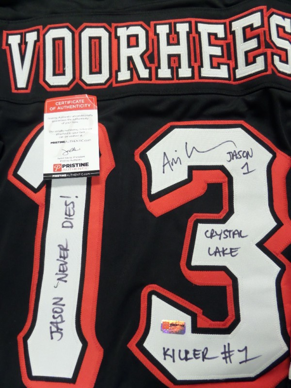 "This super cool, super rare horror thriller piece is a mint jersey, adorned in black, red and white colors, and with sewn on everything, as well as ""Voorhees"" on back. Great piece, black #13 signed in bold black sharpie, and with all kinds of great movie lingo written as a bonus in Ari Lehmans hand. It has a Pristine Auction LOA and hologram intact, and value is $600.00 on this hi-quality movie prop in which he even included some great inscriptions!"