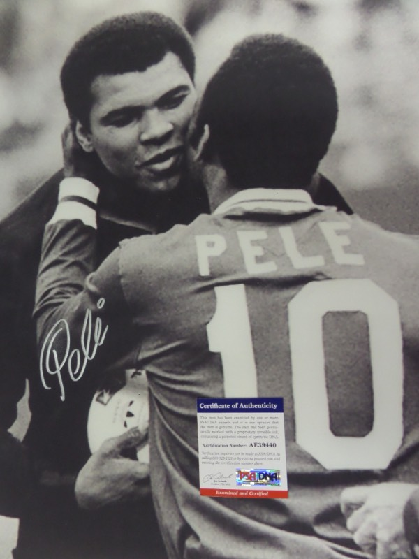 This HUGE black and white 16x20 photo shows soccer legend, Pele, embracing three time Heavyweight Champion, Muhammad Ali.  It is beautifully-penned in silver by the all time pitch great himself, and comes fully PSA/DNA certified (AE39440) for authenticity purposes.  A gorgeous display photo, ideal size for framing, and retail is well into the hundreds!