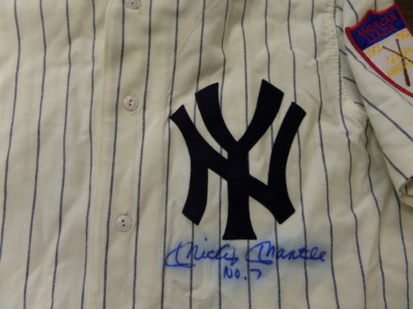 This home white size L 1951 New York Yankees throwback from Mitchell & Ness is in NM condition, and comes with everything sewn, including The Mick's 7 on the back, and an American League Golden Anniversary patch on the left shoulder.  It is front-signed in blue sharpie by the all time great himself, grading a slightly bled 6.5, with No. 7 added in his hand, and this baby will frame and show off proudly in any collection.  Valued into the low thousands!