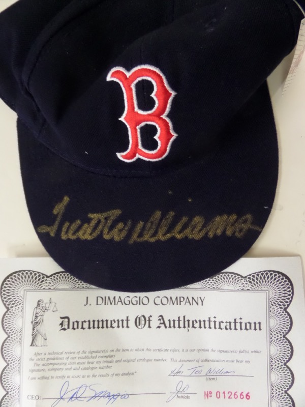 This great-looking collector's item is a NM, fitted Boston Red Sox cap from New Era's Diamond Collection, complete with original tagging still attached.  It is hand-signed in gold sharpie right on top of the bill by the 2 time Triple Crown winner himself, and comes with a COA from the J. DiMaggio Co. for authenticity purposes.  Valued well into the hundreds!