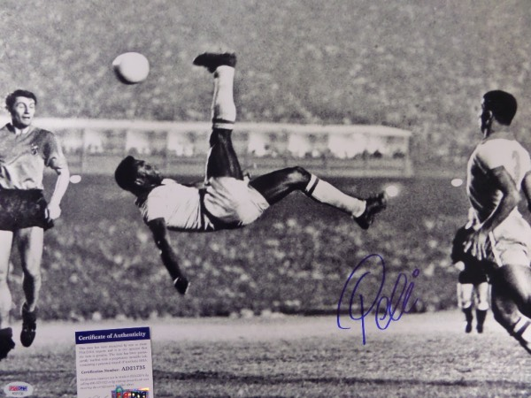 This large black and white 16x20 photo shows soccer legend Pele in a mid air bicycle kick.  It is hand-signed boldly in blue sharpie by the all time great himself, grading a strong 9 overall, and comes certified by PSA/DNA (AD 21735) for authenticity purposes.  A MUST for any soccer collection, and valued well into the hundreds!