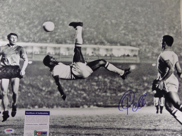 This large black and white 16x20 photo shows soccer legend Pele in a mid air bicycle kick.  It is hand-signed boldly in blue sharpie by the all time great himself, grading a strong 9 overall, and comes certified by PSA/DNA (AD 21737) for authenticity purposes.  A MUST for any soccer collection, and valued well into the hundreds!
