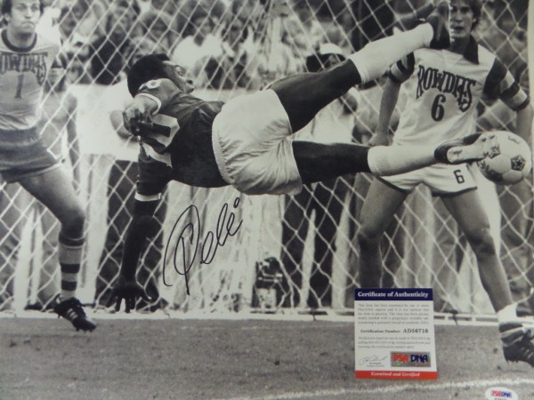 This large black and white 16x20 photo shows soccer legend Pele in a mid air kick, horizontal to the ground.  It is hand-signed boldly in black sharpie by the all time great himself, grading about an 8 overall, and comes certified by PSA/DNA (AD 56716) for authenticity purposes.  A MUST for any soccer collection, and valued well into the hundreds!