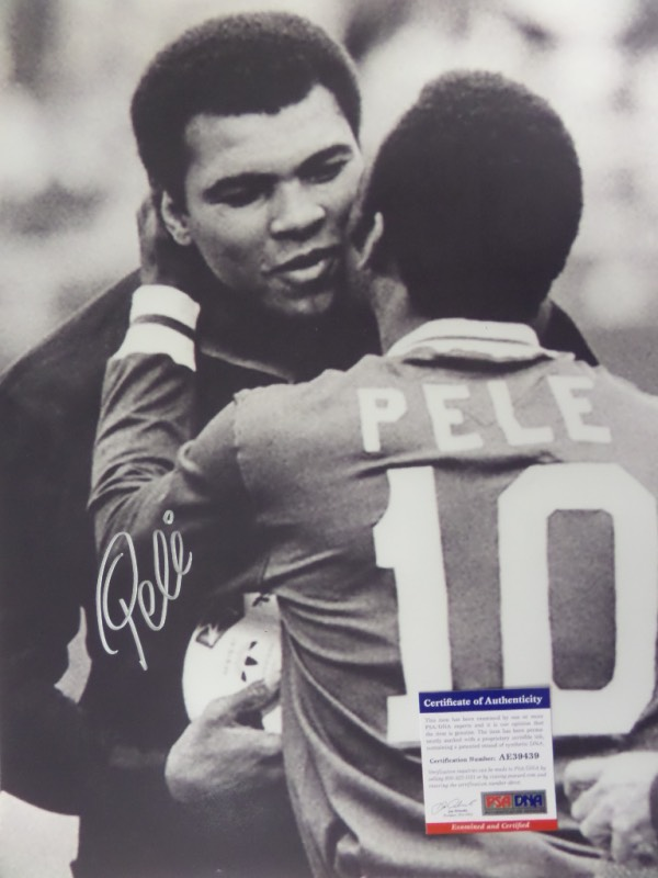This HUGE black and white 16x20 photo shows soccer legend, Pele, embracing three time Heavyweight Champion, Muhammad Ali.  It is beautifully-penned in silver by the all time pitch great himself, and comes fully PSA/DNA certified (AE39439) for authenticity purposes.  A gorgeous display photo, ideal size for framing, and retail is well into the hundreds!