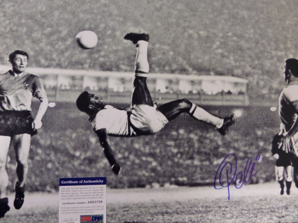 This large black and white 16x20 photo shows soccer legend Pele in a mid air bicycle kick.  It is hand-signed boldly in blue sharpie by the all time great himself, grading a strong 9 overall, and comes certified by PSA/DNA (AD 21729) for authenticity purposes.  A MUST for any soccer collection, and valued well into the hundreds!