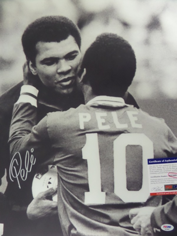 This HUGE black and white 16x20 photo shows soccer legend, Pele, embracing three time Heavyweight Champion, Muhammad Ali.  It is beautifully-penned in silver by the all time pitch great himself, and comes fully PSA/DNA certified (AE39447) for authenticity purposes.  A gorgeous display photo, ideal size for framing, and retail is well into the hundreds!