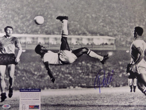 This large black and white 16x20 photo shows soccer legend Pele in a mid air bicycle kick.  It is hand-signed boldly in blue sharpie by the all time great himself, grading a strong 9 overall, and comes certified by PSA/DNA (AD 56699) for authenticity purposes.  A MUST for any soccer collection, and valued well into the hundreds!