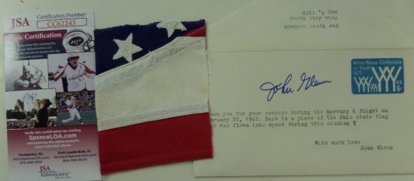 This super high value item is a 1971-72 dated envelope, and has a typed note and autograph from the deceased astronaut. The blue flair signature is a 10, Jimmy Spence and his team at JSA approved of it all, and a real piece of 1962 Ohio flag is included from Glenns collection. It was flown on Mercury 6 in 1962, and values can reach thousands on real space flown pieces, especially from a Great American Hero like John Glenn!