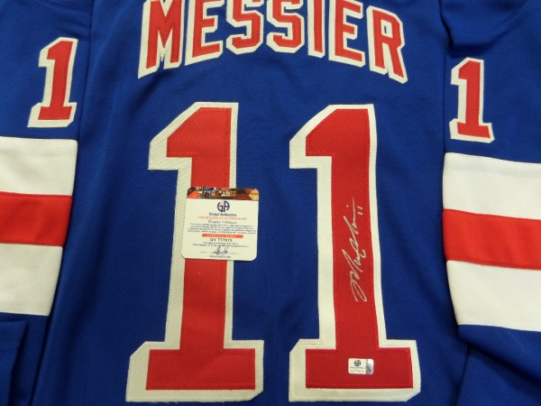 This blue custom XL New York Rangers #11 Messier jersey is in NM condition, and comes trimmed in red and white, with everything professionally hand-stitched.  It is back number-signed in silver sharpie by the HOF center and all time great, grading at least a strong 8.5 overall, and the jersey comes Global Authentics certified (GV777675) for authenticity purposes.  Valued into the high hundreds, with a low, LOW minimum bid to begin with!