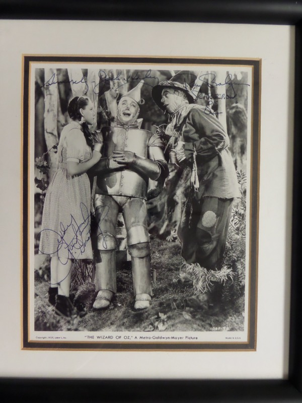 "This rare MGM publicity photo is 8x10 in size and shows ""Dorothy, the Scarecrow & Tin Man"" from the hit movie, and comes ink signed by all 3 on terrific spots. It grades close to a 9 we'll say, shows off well from 12 feet away, and even comes to you professionally double matted and framed, and certified by Living Legends as an added bonus. A must have Hollywood item, and value after framing is $2200.00."