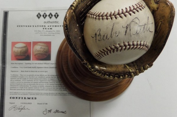 This scintilating display item is a vintage Spalding Official League Leader Baseball, hand signed across the sweet spot in black by Yankees all time great, Babe Ruth. The signature grades a faded but still legible 5.5-6, and the ball comes fully certified by STAT Authentic for certainty.  To boot, it sits in a fabulous wood holder with metal nameplate and baseball glove perch for display.  Valued into the five figure range!