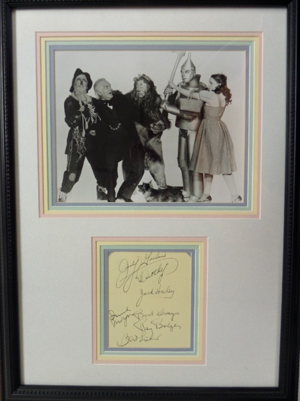 "This custom, professionally quadruple matted display is about 16x20 in size, and comes wood framed as an added bonus. It holds 2 custom cutouts from the 1939 MGM hit movie, including a large B&W cast image which shows all 5 characters, and a group signed album page featuring autographs of ""Dorothy, Tin Man, Cowardly Lion, Scarecrow and Oz"" himself. Terrific Hollywood piece, value is thousands with all 5 stars long deceased, and grade is an 8 or better all over the place."