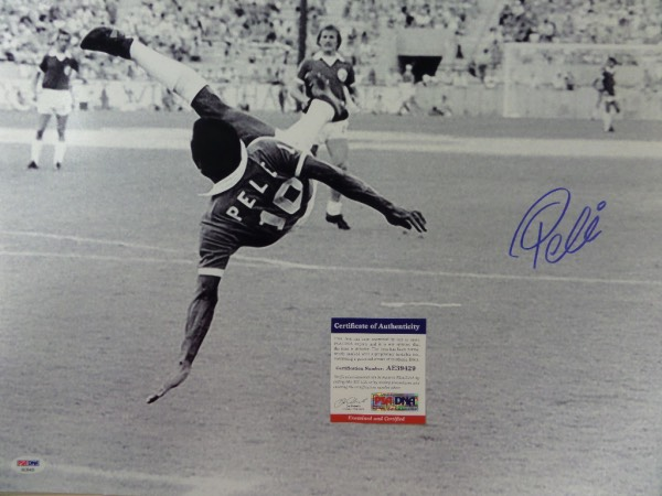 This large black and white 16x20 photo shows soccer legend Pele in a mid air kick, horizontal to the ground.  It is hand-signed boldly in blue sharpie by the all time great himself, grading about an 8 overall, and comes certified by PSA/DNA (AE 39429) for authenticity purposes.  A MUST for any soccer collection, and valued well into the hundreds!