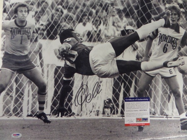This large black and white 16x20 photo shows soccer legend Pele in a mid air kick, horizontal to the ground.  It is hand-signed boldly in black sharpie by the all time great himself, grading about an 8 overall, and comes certified by PSA/DNA (AE37921) for authenticity purposes.  A MUST for any soccer collection, and valued well into the hundreds!