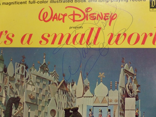 "This vintage ""It's a Small World"" LP album is from 1964 and looks just great.  It is hand-signed at the top in blue ink by none other than Walt Disney himself, grading about a 7 overall, a truly fine example of a Disney autograph, and still shows up well against the yellow part of the album cover.  With his death now exactly a half century ago, retail here is very high hundreds!"
