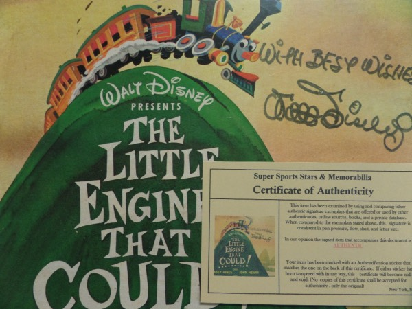 "This original ""Walt Disney Presents The Little Engine That Could!"" LP album is in EX/EX+ condition overall, and comes hand-signed in black felt tip marker by the famed entertainment icon himself.  Signature grades an overall 7, with With Best Wishes included, and the album comes with a photo COA from Super Sports Stars & Memorabilia for authenticity purposes.  Valued well into the thousands!"