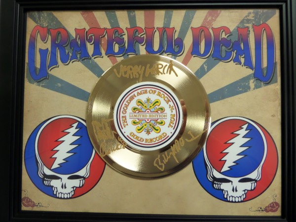 "This superb rock n' roll custom wall hanging is 16x20 in size and comes to you with a real 24 karat gold record in the center. It honors the timeless rock band on the limited edition piece, and features facsimile signatures on the record from all 4 band mates. Great colors with the matting, and perfect for all ""Deadheads""."