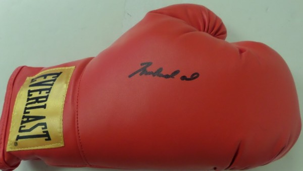 "This early 90's boxing glove is red leather, mint, and a gem from Everlast. It comes IN PERSON, boldly black sharpie signed by the ""Greatest"", and grades a clean, almost legible 9 or better. It is signed right in the center by the deceased HOF fighter, was obtained by Lee himself back in the day, and of course our famous lifetime guarantee accompanies."