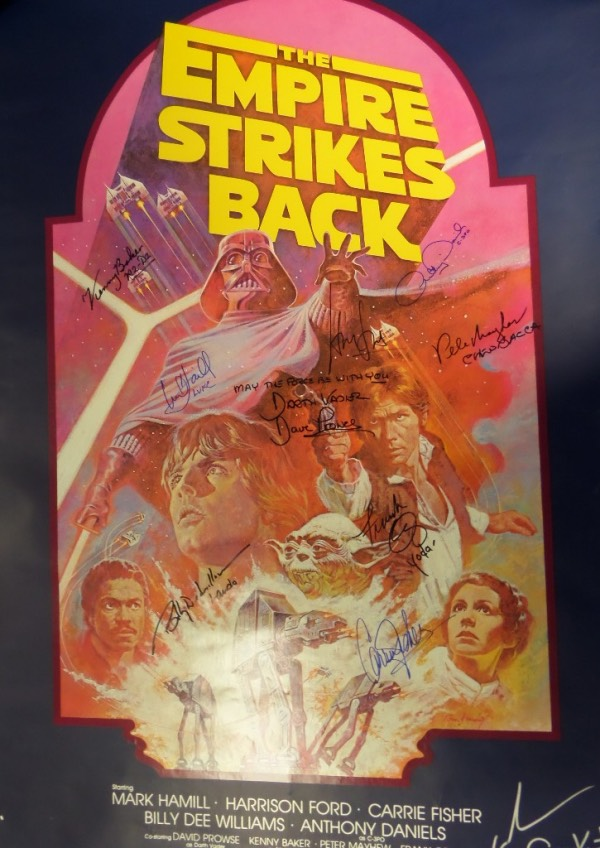 "This full size 27x40 movie poster for the 1980 Star Wars classic, ""The Empire Strikes Back"" is hand-signed in black and blue sharpie by no less than 9 stars from the film, as well as Producers George Lucas and Gary Kurtz.  Included are Mark Hamill, Carrie Fisher, David Prowse, Harrison Ford, Frank Oz, Anthony Daniels, Kenny Baker, Billy Dee Williams and Peter Mayhew.  A MUST for framing and display, and retail is thousands!"