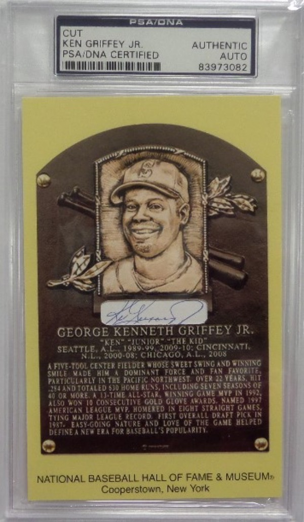 This MUST HAVE HOF item is a NM gold HOF plaque postcard of Ken Griffey Jr that features a cut in the center, hand-signed in blue ink by the Mariners all time great.  It is simply stunning, and comes slabbed authentic by the people at PSA/DNA (83973082) for your assurance.  Valued well into the hundreds!