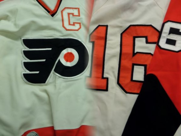 "This unbelievable attic find is a 1974 era Phila. home white, and trimmed in the usual orange and black ""Broadstreet Bullies"" colors. It has sewn on everything, shows light game usage from the HOF Stanley Cup winner, and even has the Captain ""C"" sewn on the front chest area. It shows multiple washings and number freys, and value is thousands on a possibly Stanley Cup worn item. You'll never see another one for sale-please bid accordingly!  small"