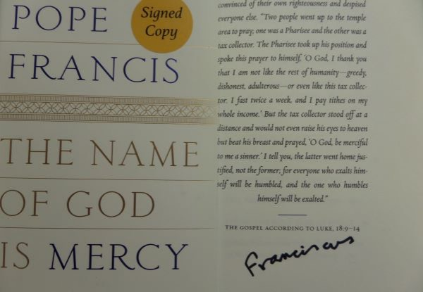 "This remarkable item is a mint hardback book, titled ""The Name of God is Mercy"", and comes black sharpie signed on the inside title page It is a 10 all over, has the ""Signed Copy"" sticker on the dustjacket, and even has a ""Compliments From""  postcard from the Pontiff himself. It is a truly terrific literary piece, and value is many times our asking price."