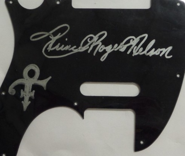 "This ultimate pop music find was obtained by a backstage insider, and signed in brilliant silver paint pen on a large, black guitar pick guard. It is signed full real name too, grade is a 10 all over, and once placed on a guitar, purple if your luck, value soars to 5 grand. Yes, he was that difficult to get!  Terrific chance, just look at our always low opening bid price, and a ""symbol"" was drawn by the Minneapolis legend as an added bonus."