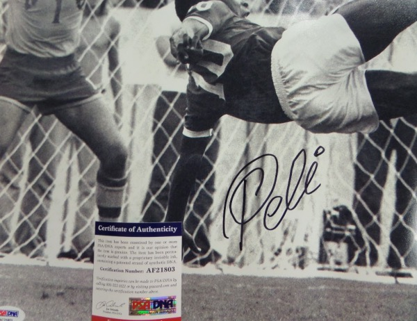 This large black and white 16x20 photo shows soccer legend Pele in a mid air kick, horizontal to the ground.  It is hand-signed boldly in black sharpie by the all time great himself, grading about an 8 overall, and comes certified by PSA/DNA (AF21803) for authenticity purposes.  A MUST for any soccer collection, and valued well into the hundreds!