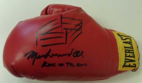 "This MINT slip on style Everlast boxing glove comes hand-signed boldly in black sharpie by ""the Greatest"" himself, 3 time Heavyweight Champion of the World, Muhammad Ali.  Signature grades about an 8-8.5, complete with a hand-drawn ring, and King of the Ring inscription, and with Ali no longer living, retail is well into the low thousands!"