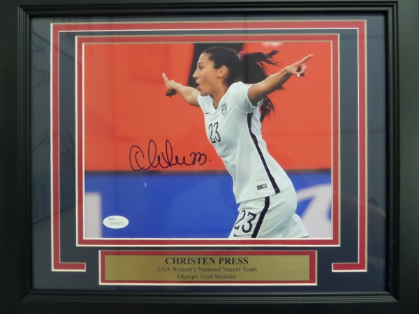 This stunning, custom, professional wall hanging comes to you triple matted and wood framed, and holds a hand signed color 8x10 of the gold medal winning soccer star. It grades a 15 on a 1-10 scale all over, shows off incredibly from across our room, and  has both the proper JSA lifetime COA and attached hologram for certainty.