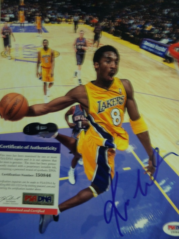 This full color 8x10 shows Kobe Bryant in mid air, about to stuff one home during a Lakers/Nets NBA Finals game.  It is hand-signed in bold blue sharpie by the HOF'er and 5 time NBA Champion himself, and is fully PSA/DNA certified (I50846) for authenticity purposes.  Since his untimely death earlier this year, anything Kobe signed has absolutely skyrocketed in value!