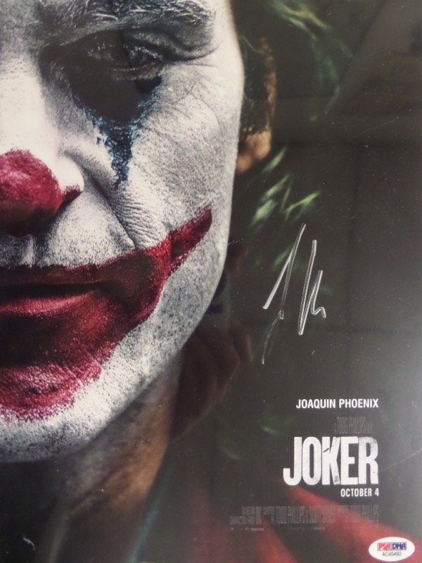 "This 11x14 color close up print of an original ""Joker"" movie poster print shows a large color image of the character's face.  It is hand-signed in silver by the man who won the Academy Award for his portrayal, Joaquin Phoenix, the signature grading about a 7, and the piece comes certified by PSA/DNA (AC45492) for authenticity purposes.  A jewel for any film collection, and valued well into the hundreds!"