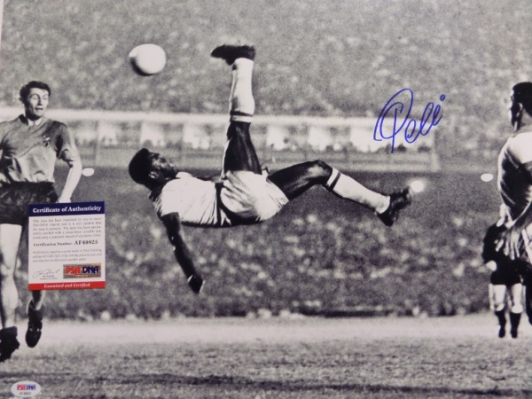 This large black and white 16x20 photo shows soccer legend Pele in a mid air bicycle kick.  It is hand-signed boldly in blue sharpie by the all time great himself, grading a strong, clean 9 overall, and comes certified by PSA/DNA (AF49825) for authenticity purposes.  A MUST for any soccer collection, and valued well into the hundreds!