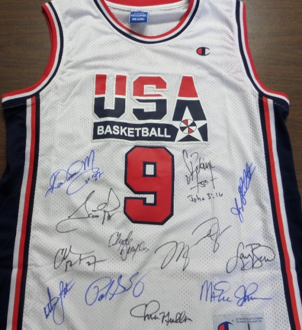 This 1992 era Champion jersey is a #9 Jordan issue, has sewn on everything, and comes black and blue sharpie signed by every gold medal winner of the 1992 Barcelona squad. I see signatures from Jordan, Bird, Magic, Mullin, Malone, Barkley, Drexkler and more, and value is just over 3 grand on the historic hardwood offering.