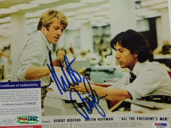 "This full color ""All the President's Men"" movie publicity 8x10 photo shows ""Woodward and Bernstein,"" portrayed by Robert Redford and Dustin Hoffman.  It is hand-signed in blue sharpie by Redford, grades a strong overall 8.5, and comes fully PSA/DNA certified (T14522) for authenticity.  Valued well into the hundreds!"