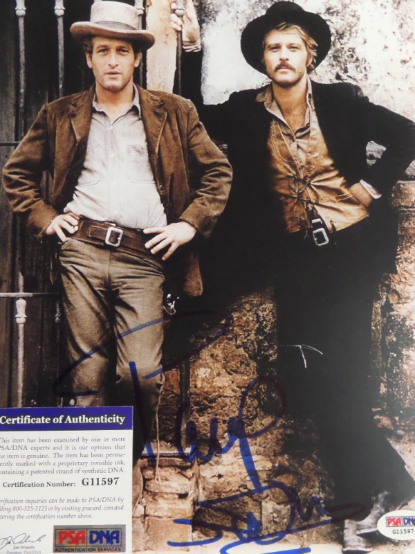 "This color 8.5x11 photo of Paul Newman and Robert Redford from the 1969 western classic ""Butch Cassidy and the Sundance Kid"" is hand-signed in blue sharpie by ""Butch"" himself, legendary actor and Academy Award winner, Paul Newman.  Signature grades about a 7.5, and the photo is certified by PSA/DNA (G 11597) for authenticity.  With Newman now deceased many years, retail is well into the hundreds!"
