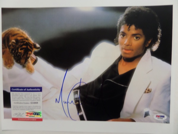 "This full color ""Thriller"" photo is a frame-ready 11x14 in size, and is an image of a black and white-clad King of Pop playing with a baby tiger.  It comes nicely-penned in blue sharpie by the longtime superstar himself, and grades a crisp and clean overall 9.  Comes with a COA from PSA/DNA (I 51988) for authenticity purposes, and with his death now more than a decade ago, retail here is low thousands!"