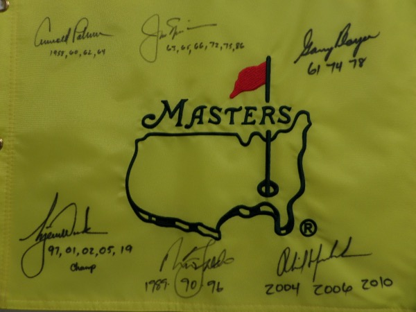 This MINT condition, authentic style yellow Masters pin flag features the Masters logo embroidered, and comes hand-signed all around in black sharpie by no less than SIX PGA greats who have won the famed Augusta major at least three times!  Included are Jack Nicklaus, Arnold Palmer, Gary Player, Tiger Woods, Nick Faldo, and Phil Mickelson, and each golfer has added the years that he won the tournament as an inscription.  NO golf collection would be complete without this crown jewel, valued into the low thousands!
