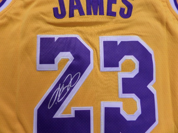 This yellow size 50 LA Lakers jersey from Nike is still tagged as NEW, and comes trimmed in purple and white, with everything professionally-stitched.  It is back number-signed in very bright silver by King James himself, grading an overall 9, and this gem is perfect for framing and display for any collection.  Valued into the low thousands!