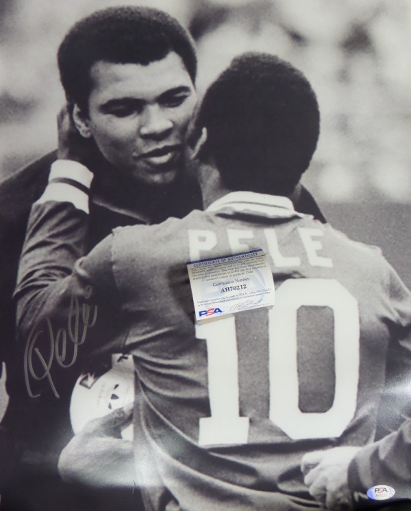 This HUGE black and white 16x20 photo shows soccer legend, Pele, embracing three time Heavyweight Champion, Muhammad Ali.  It is beautifully-penned in silver by the all time pitch great himself, and comes fully PSA/DNA certified for authenticity purposes.  A gorgeous display photo, ideal size for framing, and retail is well into the hundreds!