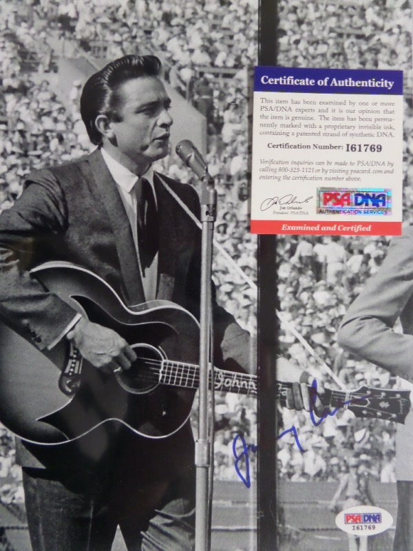 This black and white 8x10 photo shows a very young Johnny Cash performing for thousands of people.  It comes hand-signed in blue sharpie by The Man In Black himself, and grades a strong 8 at least.  A COA and sticker are included from the people at PSA/DNA (I 61769) for authenticity purposes.  Valued well into the hundreds!