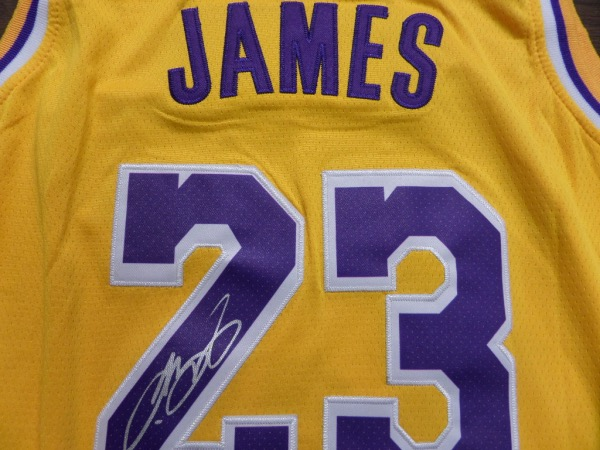 This yellow size 50 LA Lakers jersey from Nike is still tagged as NEW, and comes trimmed in purple and white, with everything professionally-stitched.  It is back number-signed in silver by King James himself, grading an overall 8.5 at least, and this gem is perfect for framing and display for any collection.  Valued into the low thousands!